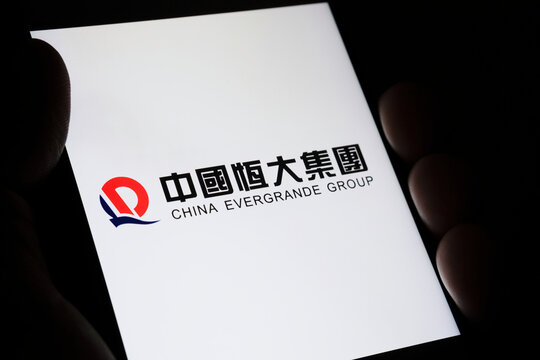 CHINA EVERGRANDE GROUP logo with its name in Chinese seen on smartphone hold in hand in a dark room. Concept. Selective focus. Stafford, United Kingdom, September 26, 2021.