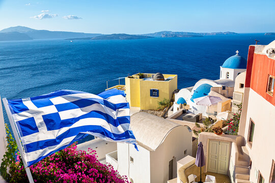 Oia village with famous white houses, bougainvillea flower and blue dome churches on Santorini island, Aegean sea, Greece. Greece flag on the foreground