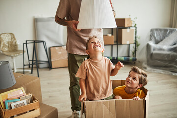 Fototapeta Portrait of two cheerful boys playing in big cardboard box while family moving to new house, copy space obraz