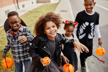 Fototapeta Group of smiling African-American kids trick or treating outdoors and walking to camera holding pails obraz