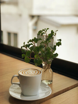The hot caramel macchiato cup, decorated with milk foam and sprinkled with coffee powder, gives a very pleasant feeling to drink with copy space