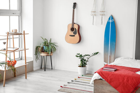 Interior of modern stylish bedroom with surfboard