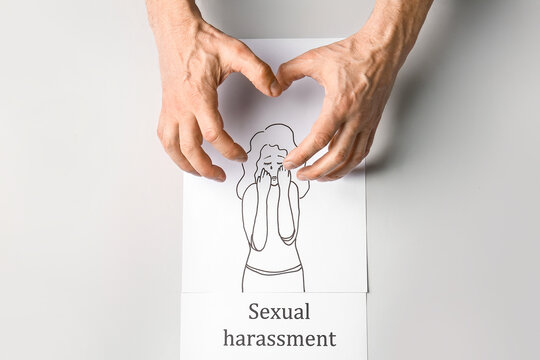 Male hands with drawing of woman and text SEXUAL HARASSMENT on light background