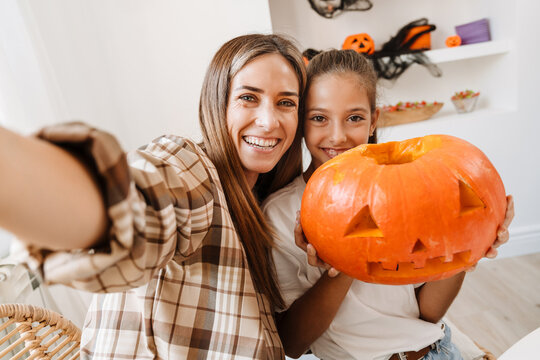 White mother and daughter taking selfie while getting ready for Halloween