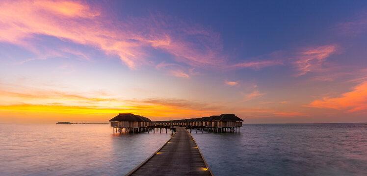 Maldives island sunset. Water bungalows resort at islands beach. Indian Ocean, Maldives. Beautiful sunset landscape, luxury resort and colorful sky. Artistic beach sunset under wonderful sky