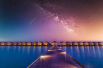 Luxury over water villas, bungalows sea ocean with beach at night sunset time, Milky Way. Exotic...