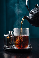 hot tea is poured into a glass with steam