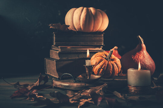 Still life for Halloween and Thanksgiving with old books, pumpkins and candle