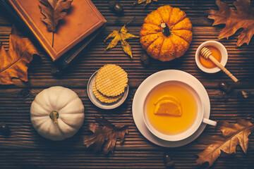Fototapeta Hot lemon tea with fall foliage and pumpkins on wooden background obraz