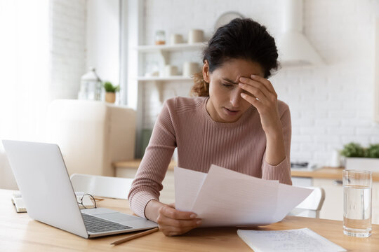 Unhappy millennial female work on laptop at home office read bad news in paper document or correspondence. Upset young Caucasian woman frustrated with negative message in paperwork. Failure concept.