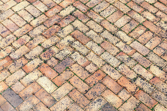 Stone wall background off old weathered distressed red brown brick with a herring bone paving pattern, stock photo image