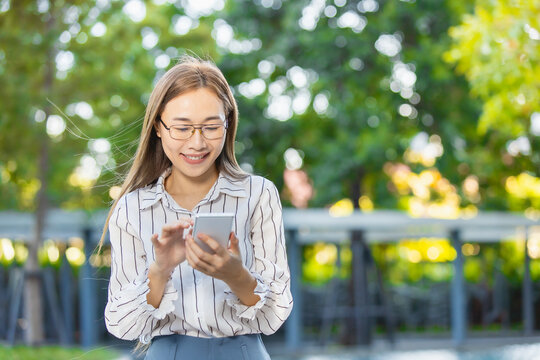 Asian business woman happy smiling looking at smartphone standing park outdoor green nature background