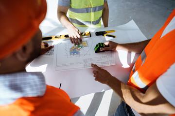 Fototapeta Close up of three man engineers looking at blueprint on construction site obraz