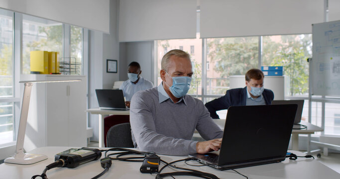 Office workers in protective mask enter workspace and sitting down at desk