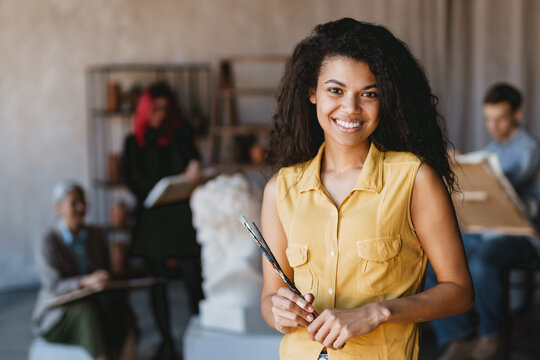Young student woman smiling at camera during class in art school