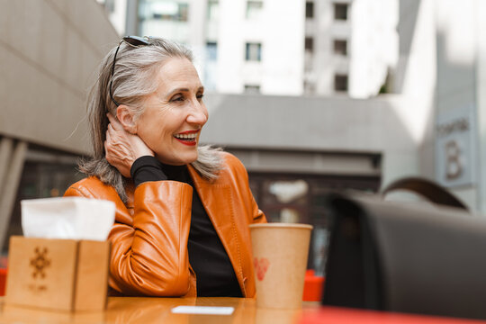 Grey white senior woman laughing while sitting in cafe