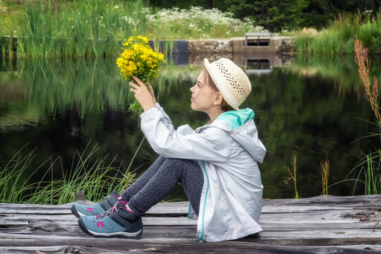 Beautiful little girl with a hat, taking a rest while sitting on a wooden pier of a mountain lake holding a bouquet of herbs