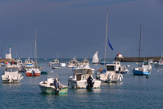 Boats at high tide and lighthouse in the port of Barfleur, a commune in the peninsula of Cotentin in the Manche department in Lower Normandy in north-western France