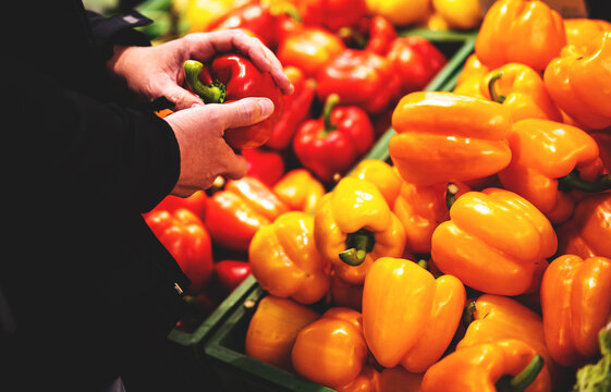 man hand holding sweet red pepper in grocery store in supermarket
