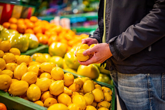 man hand holding lemon in grocery store in supermarket