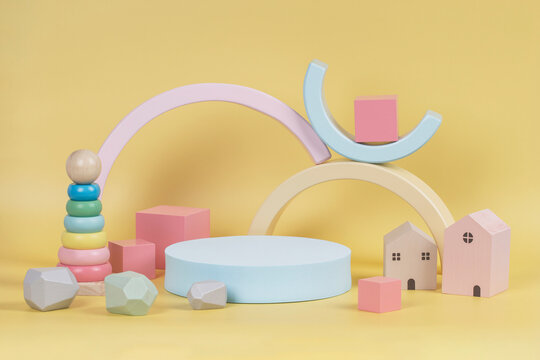 Composition of colorful educational natural wooden toys and geometric shape podium, platform on pastel yellow background. Front view