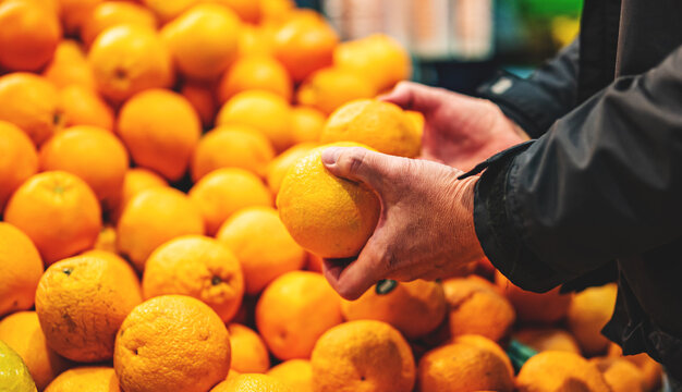 man hand holding orange in grocery store in supermarket