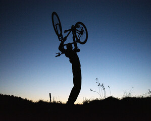 Fototapeta A man lifting a bicycle over his head shows victory obraz