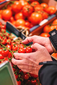 man hand holding cherry tomato in grocery store in supermarket