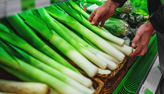 man hand holding leek in grocery store in supermarket