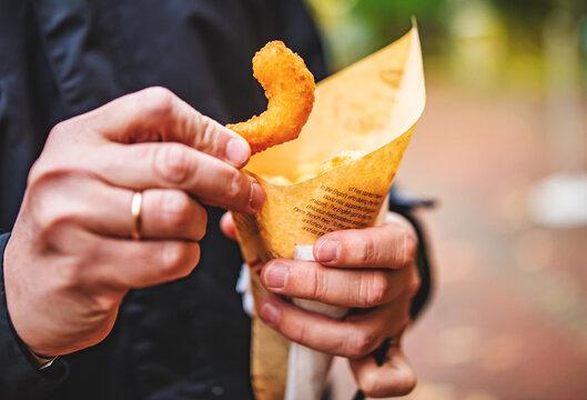 man hand holding Street food fried shrimp
