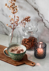 Fototapeta Morning cozy kitchen interior. Cappuccino, lit candle, cookies in a jar, dried flowers in a vase on the table obraz