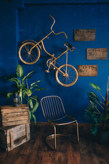 golden retro bike hanging on the blue wall