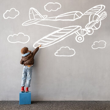 Happy kid draws a chalk airplane on the wall
