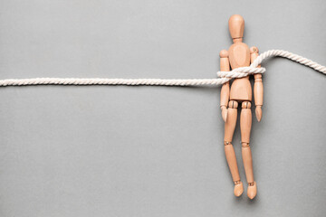 Fototapeta Mannequin with tied around rope on grey background. Concept of hostage obraz