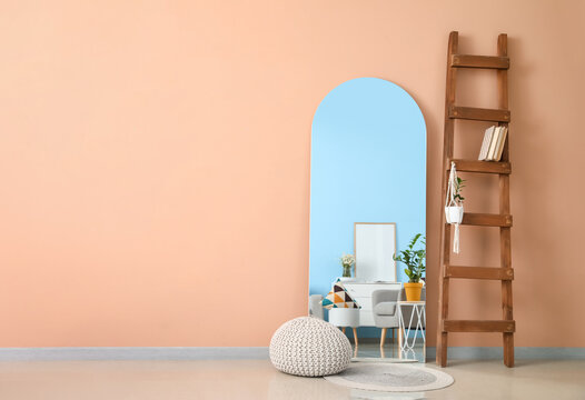 Stylish mirror with ladder in interior of light living room