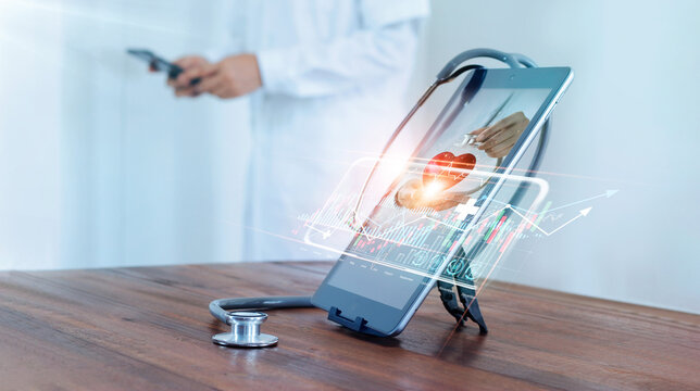 Medical examination and healthcare business via virtual interface technology.Doctor with stethoscope check and analysing patient heart health and increasing growth graph medical business on tablet.