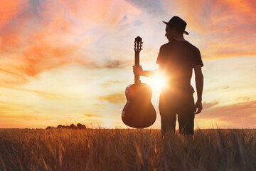 Fototapeta play music, silhouette of musician with guitar at sunset field outside obraz