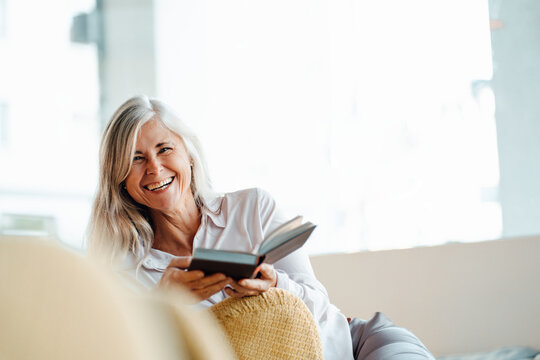 Happy mature woman sitting with book on chair in cafe