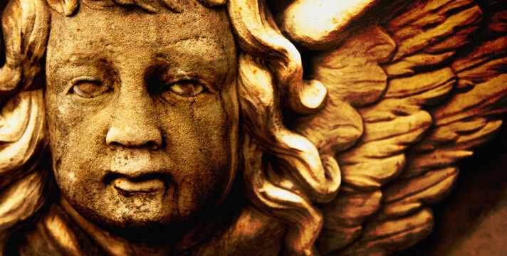 Face of angel of death. Close up. Fragment of an ancient statue.