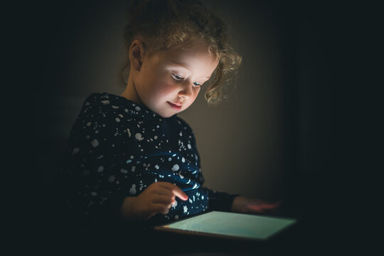 Child girl with tablet in a dark room. The baby's face is illuminated by a gadget.