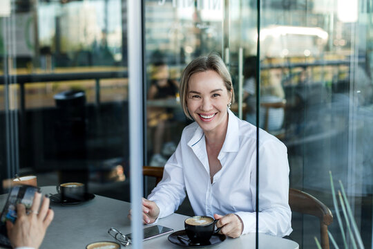 Smiling businesswoman having coffee with coworker at cafe