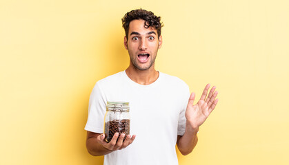 hispanic handsome man feeling happy and astonished at something unbelievable. coffee beans bottle