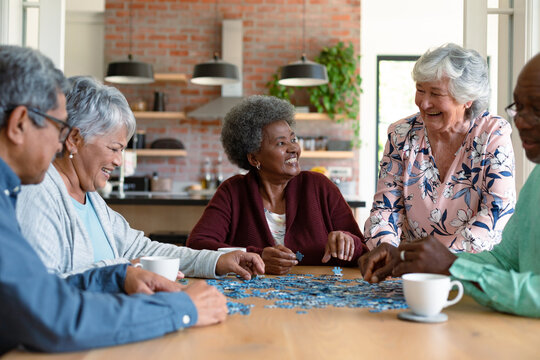 Group of diverse senior male and female friends doing puzzles at home
