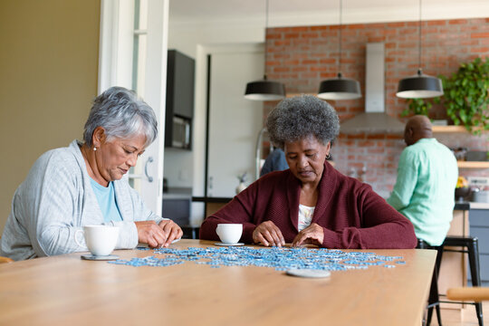 Two diverse female friends sitting in kitchen with coffee and doing puzzles
