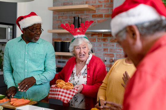 Three diverse senior male and female friends in christmas hats cooking together in kitchen