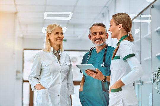 Three healthcare workers stand using tablet computer together in a hallway in the hospital.