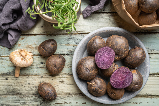 Close up of farm fresh purple potatoes in a bowl on white wooden background, top view