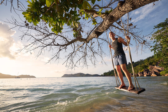 Beautiful sunny day on beach. Happy man on swing enjoying holiday in Seychelles..