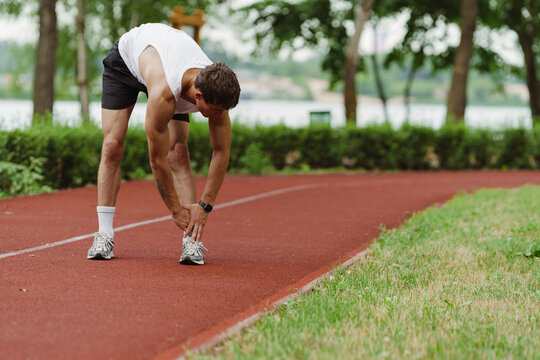 Young white sportsman doing exercise while working out on running track