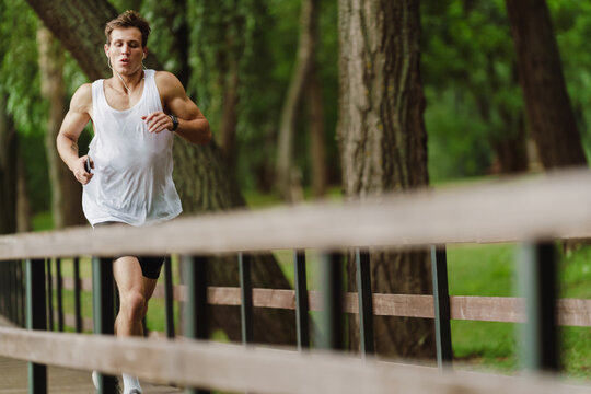 Young white sportsman listening music while running in green park